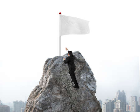 wanting: Businessman hand wanting for victory white flag on mountain peak with sky cityscape background Stock Photo