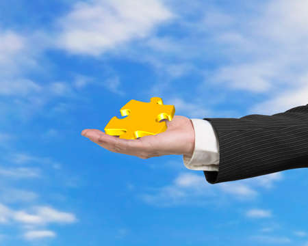 Hand showing gold jigsaw puzzle piece with blue sky clouds background photo