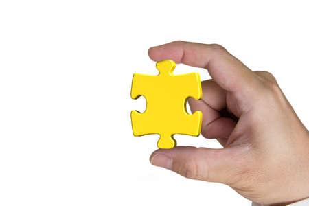 Hand holding gold jigsaw puzzle piece isolated on white background photo