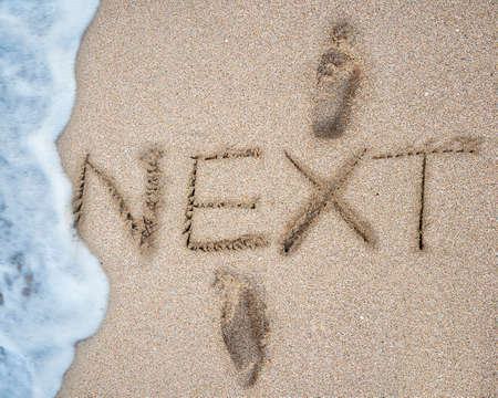 The word NEXT and footprints on the sand beach with white wave foam background photo