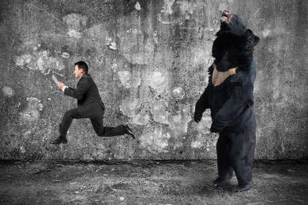 angry bear: El hombre de negocios la celebraci�n de la tableta que va desde un oso enojado con muro de hormig�n gris moteado y el fondo piso Foto de archivo