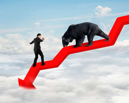 bearish market: Businessman against black bear on red arrow downward trend line with sky cloudscape background. Fight back bearish market concept.