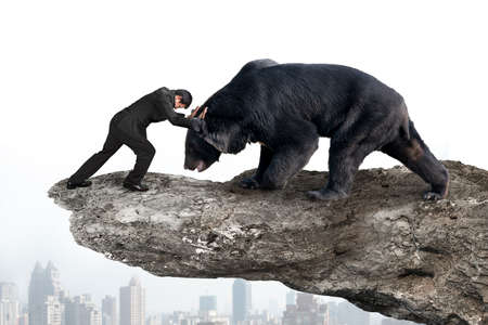 Businessman fighting against black bear on cliff with sky cityscape background