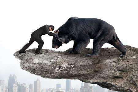 Zakenman vechten tegen zwarte beer op de klif met sky stadsbeeld achtergrond