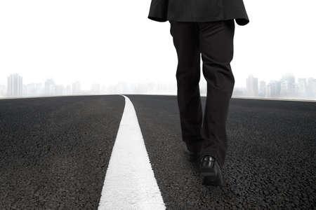 Affärsman gå på asfalterad väg med vit linje och stadsbilden