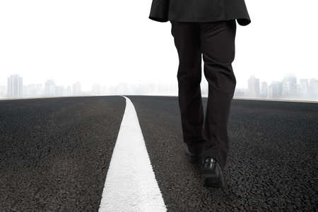 hombre solo: Empresario caminando en la carretera de asfalto con la línea blanca y escena urbana Foto de archivo