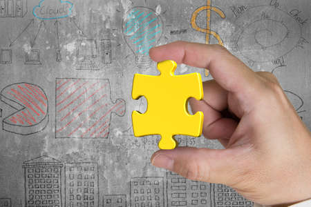 puzzling: Hand holding gold jigsaw puzzle piece with business concept doodles wall background