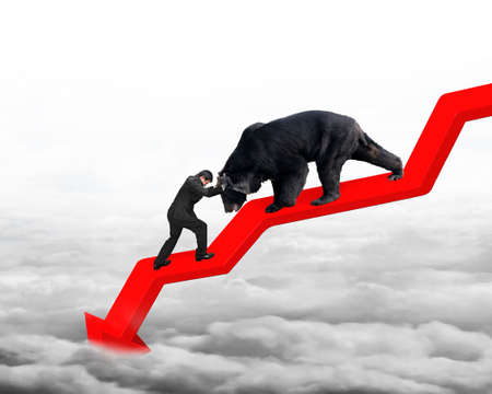 Businessman against black bear on red arrow downward trend line with gray cloudscape background. Fight back bearish market concept.