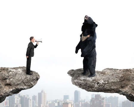 Businessman using megaphone yelling at black bear on cliff with cityscape background Stock Photo