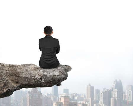 persona sentada: Vista trasera de negocios sentado en el acantilado con los rascacielos urbanos fondo Foto de archivo
