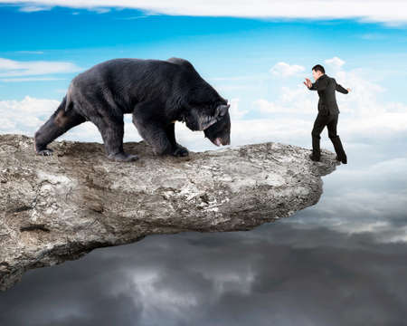 Businessman against black bear balancing on cliff with sky cloudscape background photo