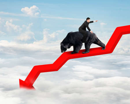 bearish market: Businessman riding black bear on red arrow downward trend line with sky cloudscape background. Fight back bearish market concept.