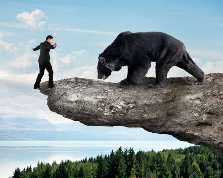 angry bear: Businessman against black bear balancing on cliff with sky trees landscape background
