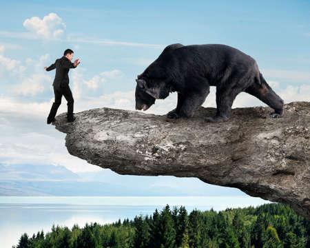 oso negro: El hombre de negocios contra el oso negro de equilibrio en el acantilado con el fondo �rboles cielo paisaje