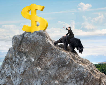 bearish market: Businessman riding black bear pursuing gold dollar sign on mountain peak with sky clouds background. Fight back bearish market concept.