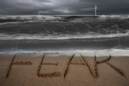 Fear word hand written on sand beach with dark stormy ocean background