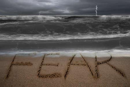 두려움 단어 손을 어두운 폭풍우 치는 바다 배경으로 모래 해변에 작성