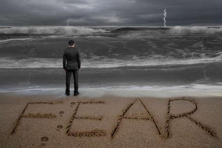 Rear view of black suit businessman standing facing fear word written on sand beach dark stormy ocean background Stockfoto