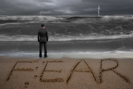 Rear view of black suit businessman standing facing fear word written on sand beach dark stormy ocean background Banque d'images