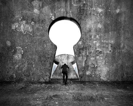 Uomo d'affari che spinge la porta del buco della serratura con la vista delle costruzioni della città sul fondo chiazzato del muro di cemento
