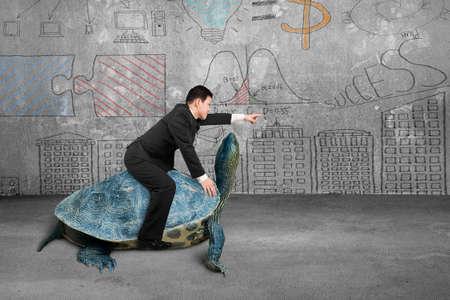 사업가 거북이를 타고 콘크리트 룸과 비즈니스 개념 낙서 벽 배경에 손가락으로 표시
