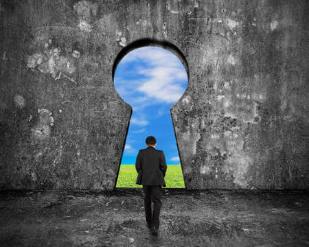 Businessman walking toward keyhole door with natural sky clouds grass view on mottled concrete wall background Stock Photo