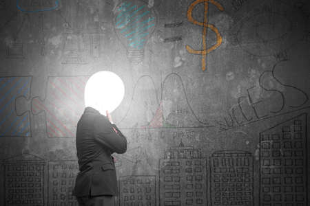 Thinking businessman with lamp head illuminated the dark business concept doodles concrete wall background photo