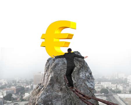 euro symbol: Businessman walking and balancing on old iron chain toward golden euro symbol of mountain peak with cityscape background