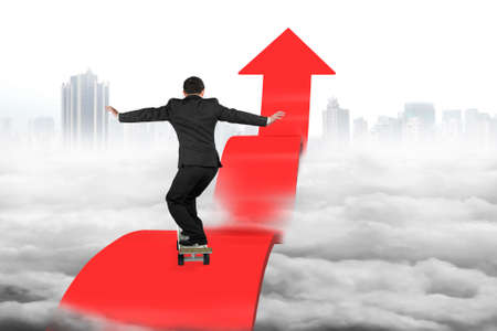 Businessman skateboarding on red arrow pointing up with cloudy cityscape background photo