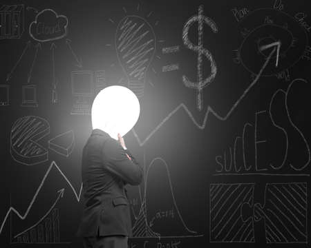 Thinking businessman with lamp head illuminated the dark business concept doodles blackboard background photo