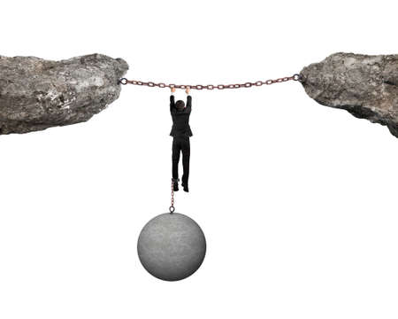 shackled: Businessman shackled by heavy concrete ball hanging on iron chains connected two cliffs with white background Stock Photo
