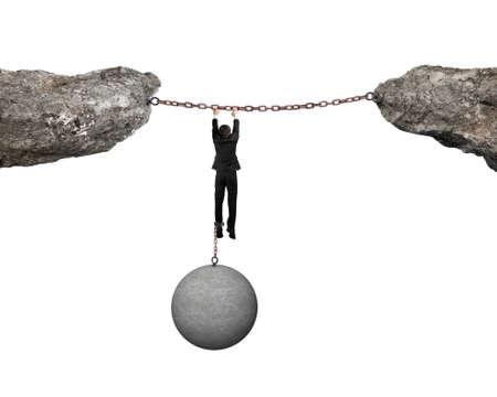 shackled: Empresario esposado por la bola hormig�n pesado colgando de cadenas de hierro conecta dos acantilados con fondo blanco