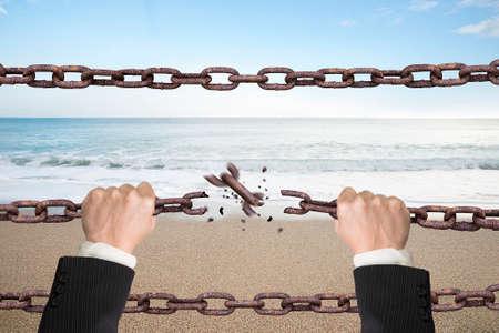 cadena rota: Cadenas de hierro oxidados rotas por las manos con el cielo de fondo naturales de mar