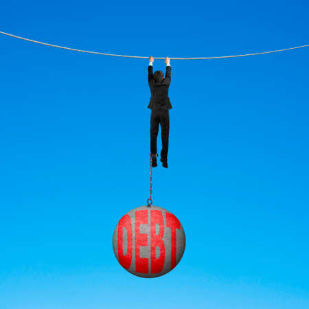 Businessman shackled by debt concrete ball hanging on the rope with blue background Stock Photo