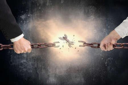 competition: Empresario tirando cadenas de hierro oxidado roto con rojo brillante luz de la chispa en el fondo muro de hormigón moteado oscuro, tira y afloja, competitivo concepto de negocio