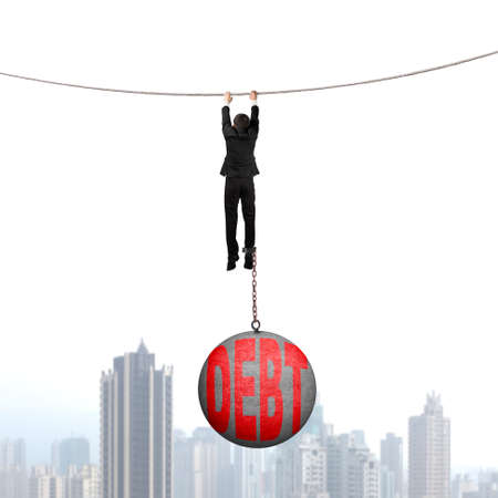 shackled: Businessman shackled by debt concrete ball hanging on the rope with urban scene background