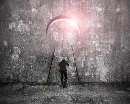 Zakenman duwen sleutelgat deur met helder zonlicht op gevlekt betonnen muur achtergrond
