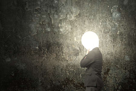 Thinking businessman with lamp head illuminated the dark mottled concrete wall background photo