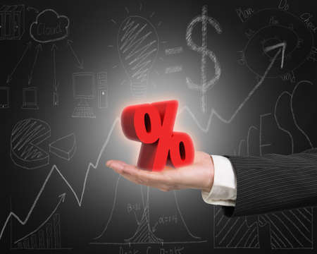 probability: Hand showing 3D red percentage sign with business concept doodles blackboard background