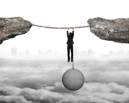 shackled: Businessman shackled by heavy concrete ball hanging on iron chains connected two cliffs with cloudy cityscape background Stock Photo