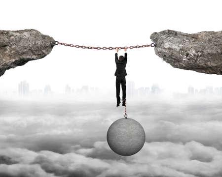 shackled: Empresario esposado por la bola hormig�n pesado colgando de cadenas de hierro conecta dos acantilados con fondo paisaje urbano nublado