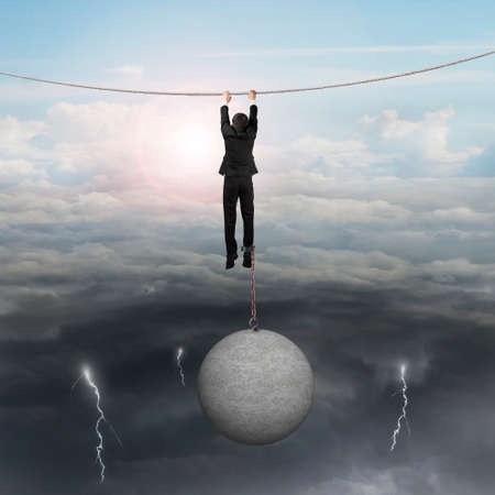 fetter: Businessman shackled by heavy concrete ball hanging on the rope with opposite weather conditions sky background, bright sun cloudscape and dark cloudy lightning.