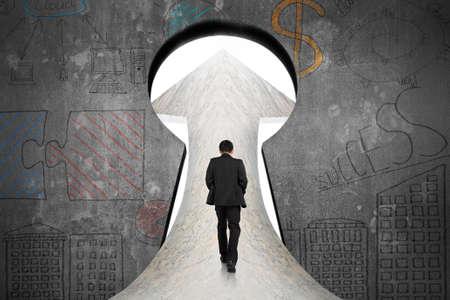 empresarios: Empresario caminando en el camino de m�rmol hacia la puerta con cerradura concepto de negocio doodles fondo de la pared de concreto Foto de archivo