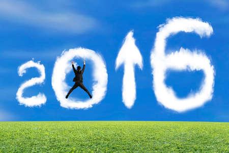 herbe ciel: Sautant d'affaires applaudir pour 2016 arrow up signe forme des nuages ??avec le ciel bleu fond d'herbe Banque d'images