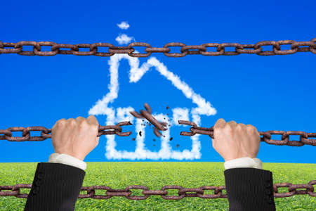 herbe ciel: Rusty iron chains broken off by hands with house shape white clouds on sky grass background