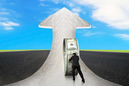 upward struggle: Businessman pushing money circle on arrow up sign marble road with asphalt pavement and sky clouds background