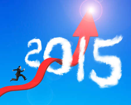 unstoppable: Businessman running on red arrow upward bending trend line breaking through 2015 shape clouds and blue sky sunlight background Stock Photo