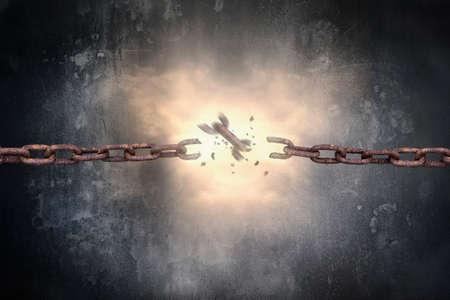 in chains: Cadenas de hierro oxidado roto con rojo brillante luz de la chispa en el fondo muro de hormigón moteado oscuro Foto de archivo