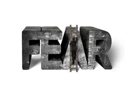 arduous: Businessman climbing wooden ladder conquering 3d fear mottled concrete word isolated on white background, overcoming fear concept.