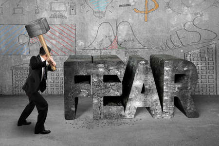 Businessman holding sledgehammer hitting 3d fear mottled concrete word with business doodles wall background, overcoming fear concept.